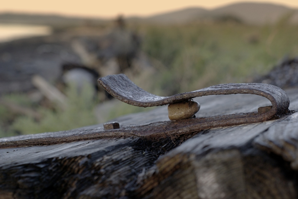 Bent iron strap trapping a pebble. Samish Island.